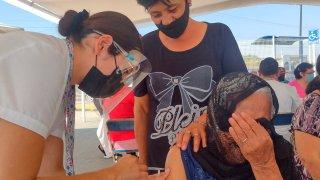 Una mujer anciana se cubre la cara mientras la vacunan